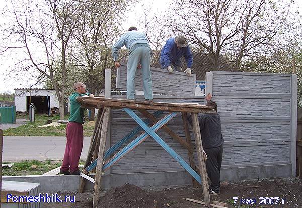 Устанавливаем бетонные плиты забора
